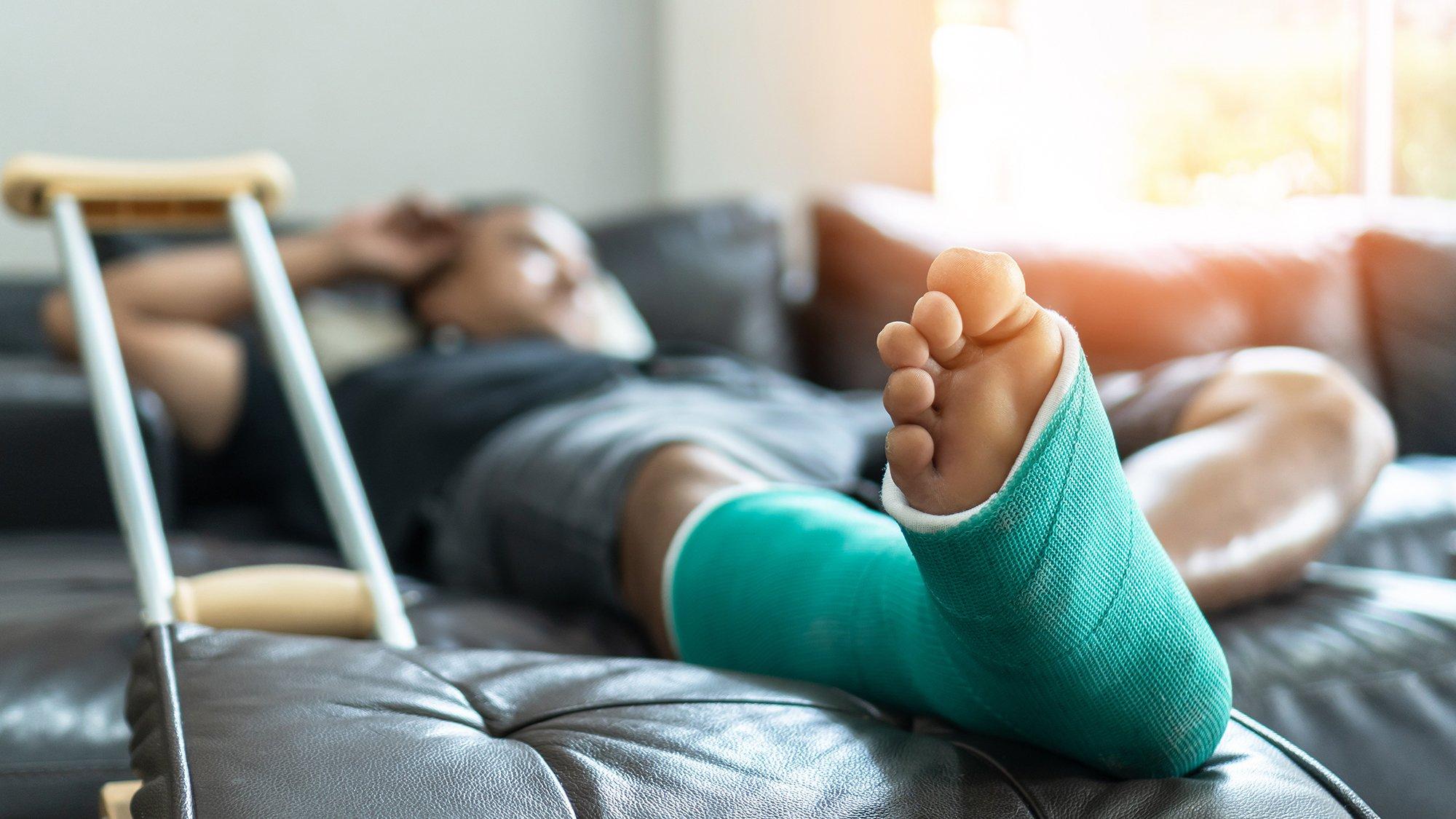 Header Bild DGUV: Mann liegt mit gebrochenem Bein auf dem Sofa